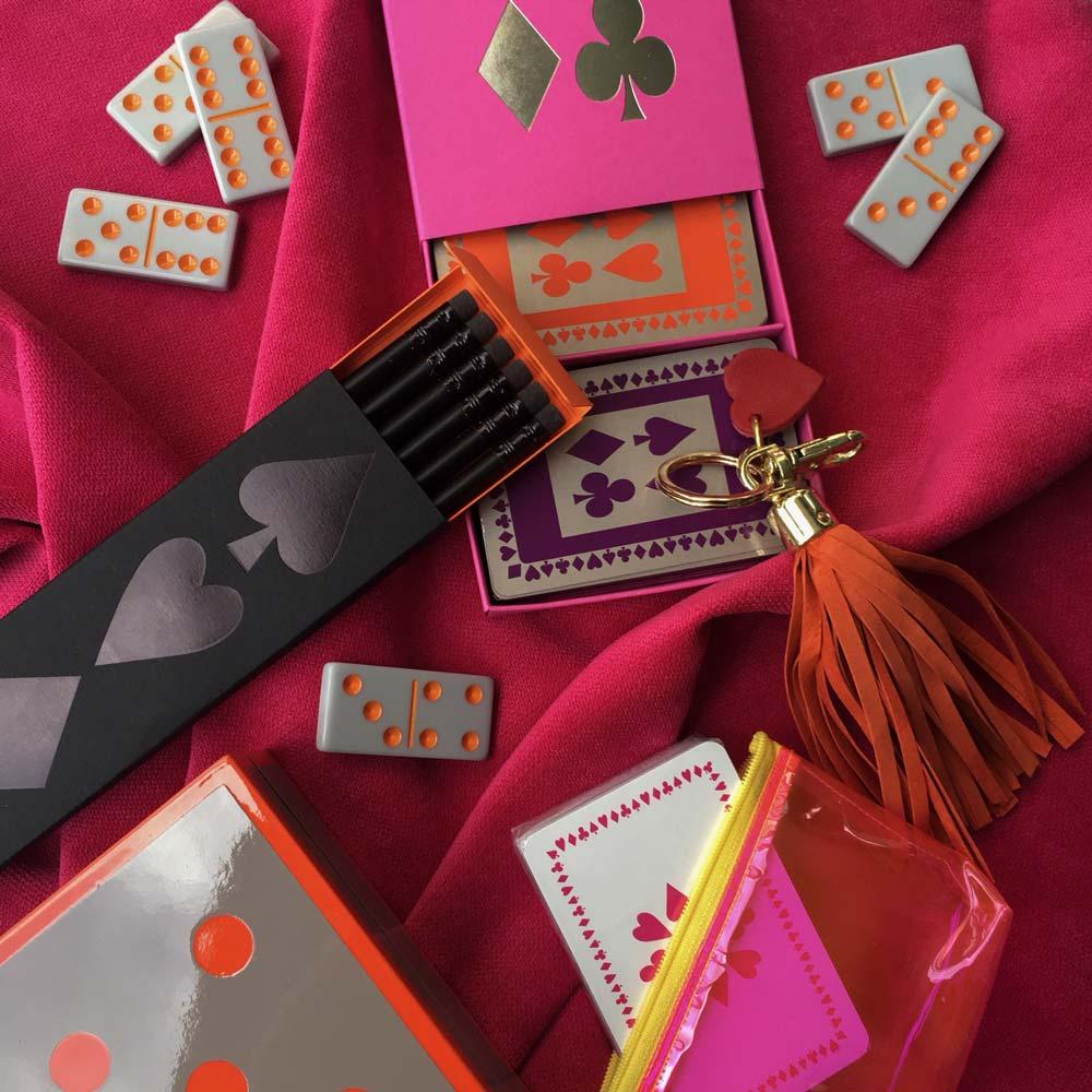 Flatlay of fuchsia bridgecloth with orange domino set, orange tassell keyring, orange and purple playing cards in pink box and box of pencils with orange sleeve liner.