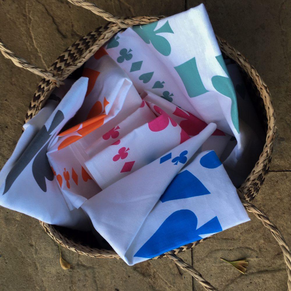Five different coloured linen union tea towels in a basket