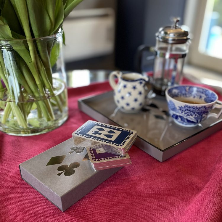 Grey sleeved box with silver gilt playing cards, showing navy and purple designs, with tray and coffee pot and cup in background