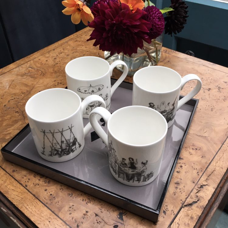 Wooden table with four bone china white mugs with black and white drawings of card players, one mug for each season on a grey lacquer square tray with posy of dahlias in glass vase in background.