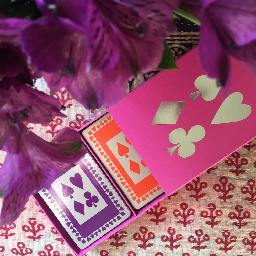 A fuchsia sleeved card box with four silver card suits on the lid and containing two decks of cards, one in orange and one in purple. Happy clashing colours!