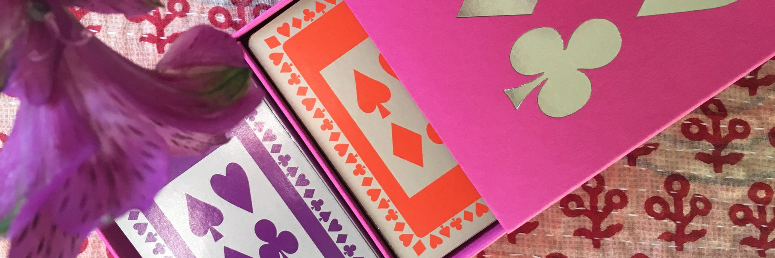 Masthead picture of purple and orange playing cards in pink box