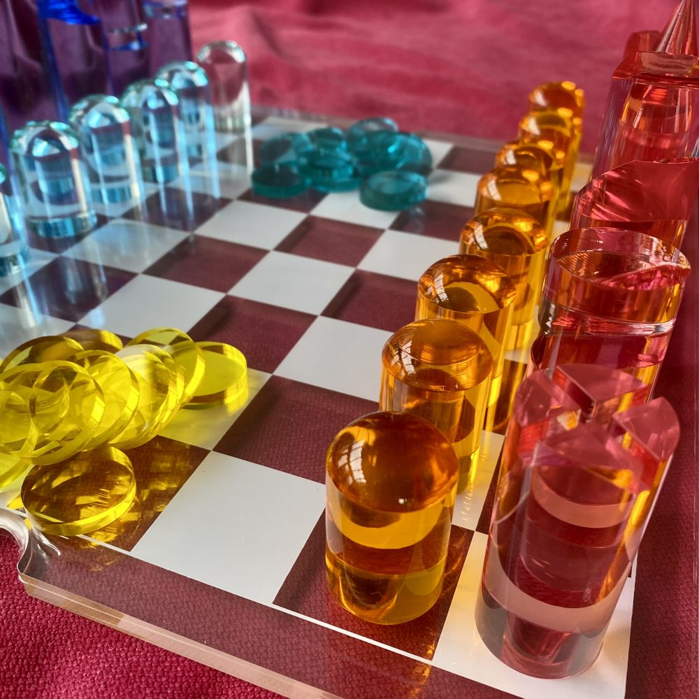 Chess and checkers set made of acrylic lucite with blues, orange and pink colour pieces on transparent and white squared lucite board