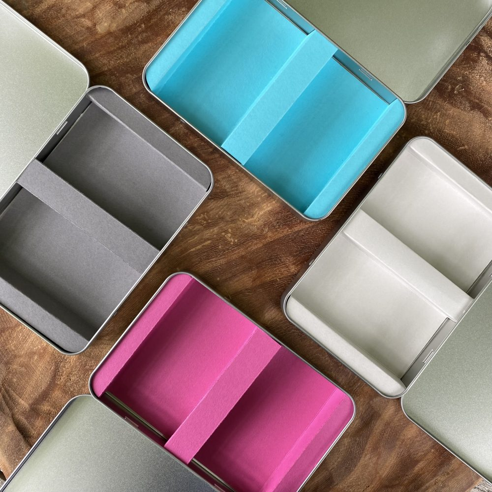 photo showing four different card inserts for the tins, pink, turquoise, dark grey and pale grey