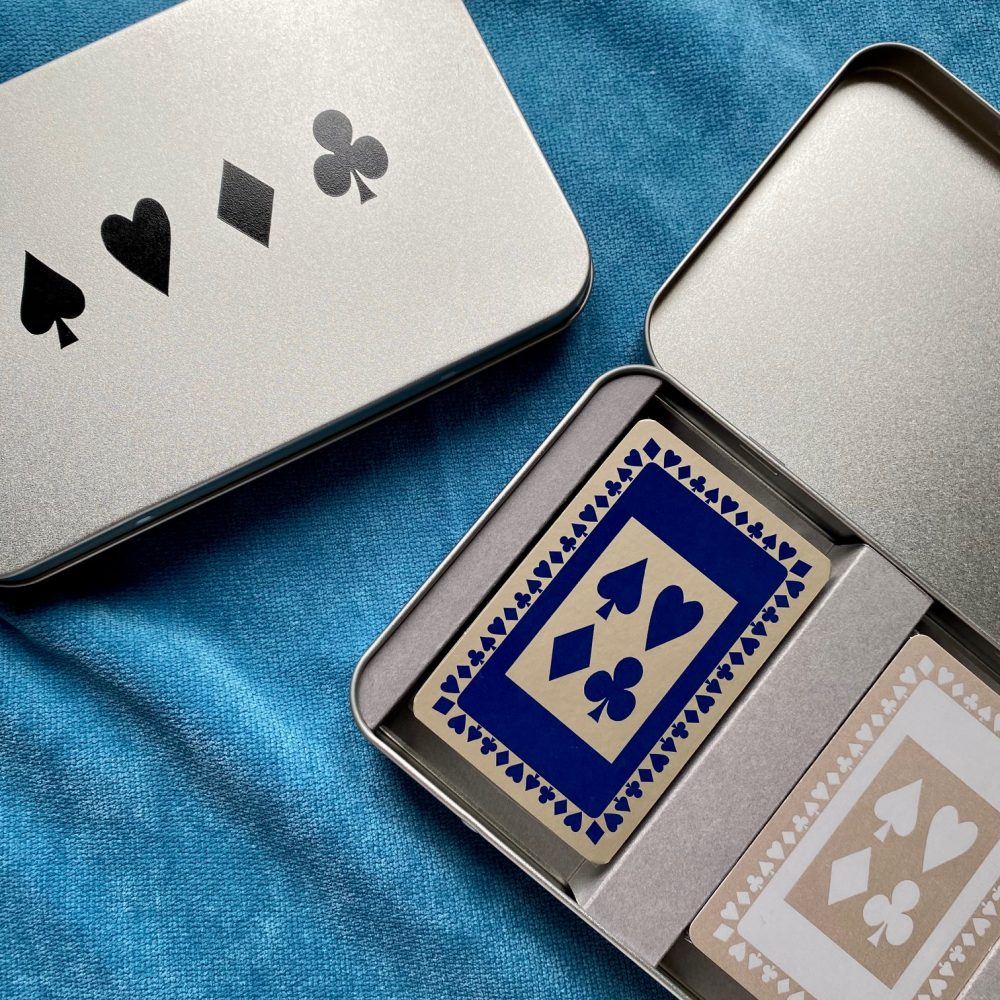 Close up shot of tin with black card suit design on lid and containing two decks of playing cards, one in navy and one in grey.