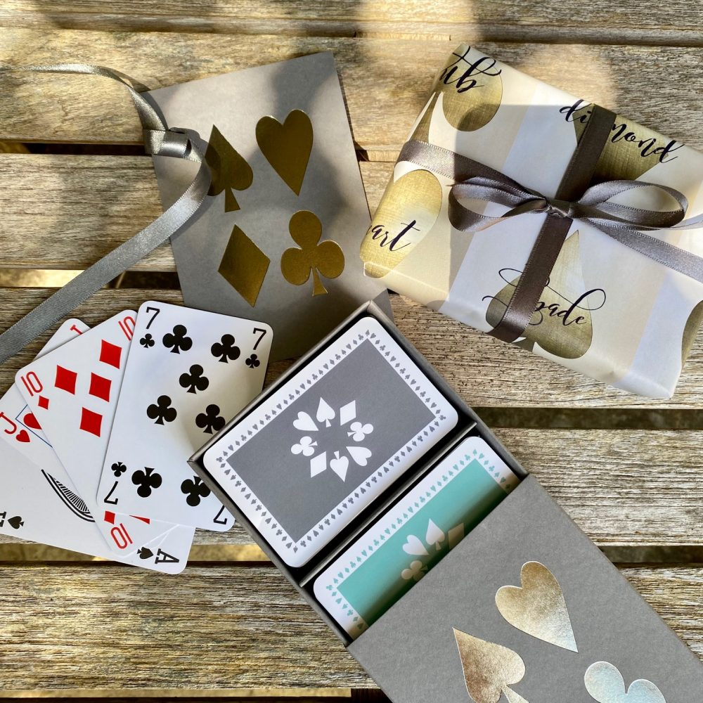 Grey sleeve box with silver card suit design on lid, containing twin pack of luxury playing cards in grey and jade green