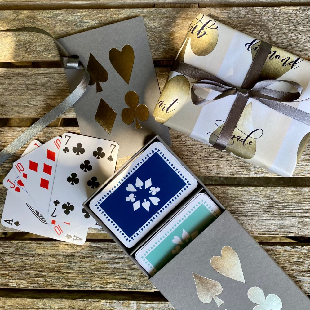 Grey sleeve box with silver card suit design on lid, containing twin pack of luxury playing cards in navy and jade green