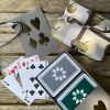 Grey sleeve box with silver card suits on lid, containing twin pack of grey and dark green luxury playing cards