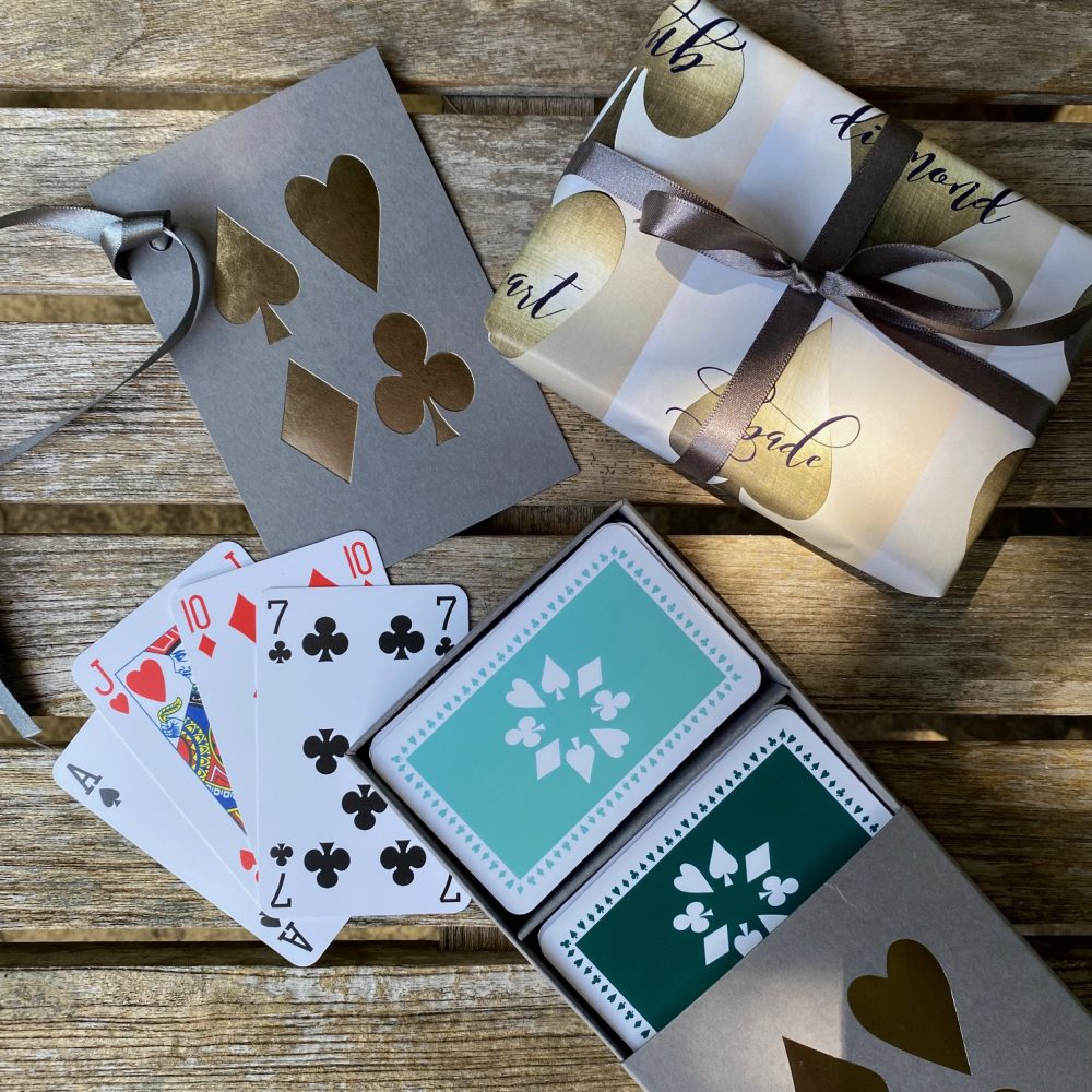 A grey sleeed box containing two pack of playing cards in dark green and jade green. The box has silver foiled card suit images on the lid.
