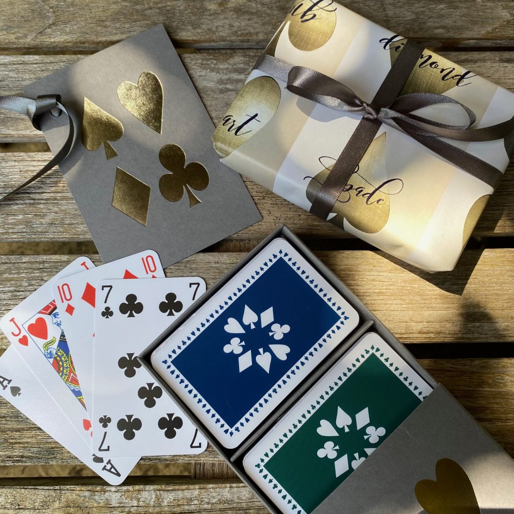 Grey sleeve box, silver suit images on the lid, containing navy and dark green luxury playing cards