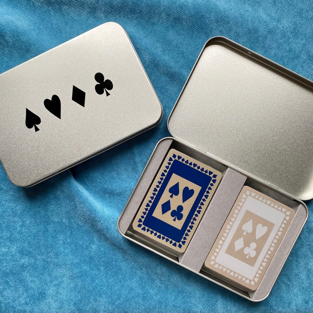 A tin with a card suit design in black on the lid and containing two decks of playing cards in navy and grey