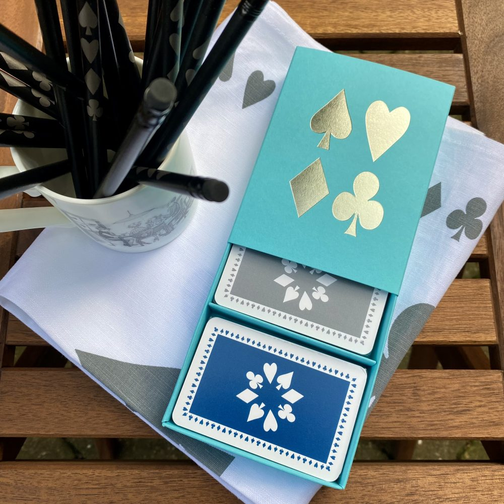 turquoise sleeved box with blue and grey playing cards and mug of pencils